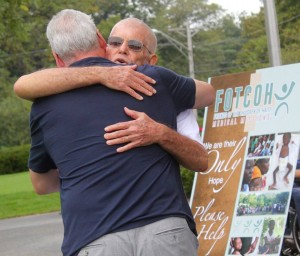 Dick hugging with sign in background