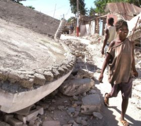 ERIC BEHRENS / JOURNAL STAR A girl walks by a building that collapsed in Jacmel, Haiti during the earthquake that devastated the island nation in January, 2010.